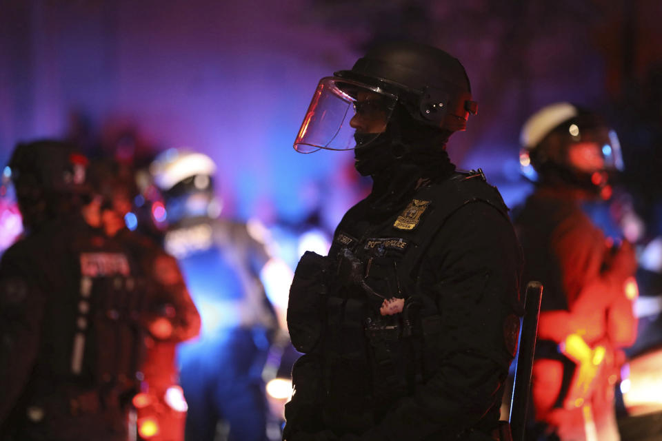 A Portland Police officer watches protesters rallying at the Mark O. Hatfield United States Courthouse on Saturday, Sept. 26, 2020, in Portland, Ore. (AP Photo/Allison Dinner)