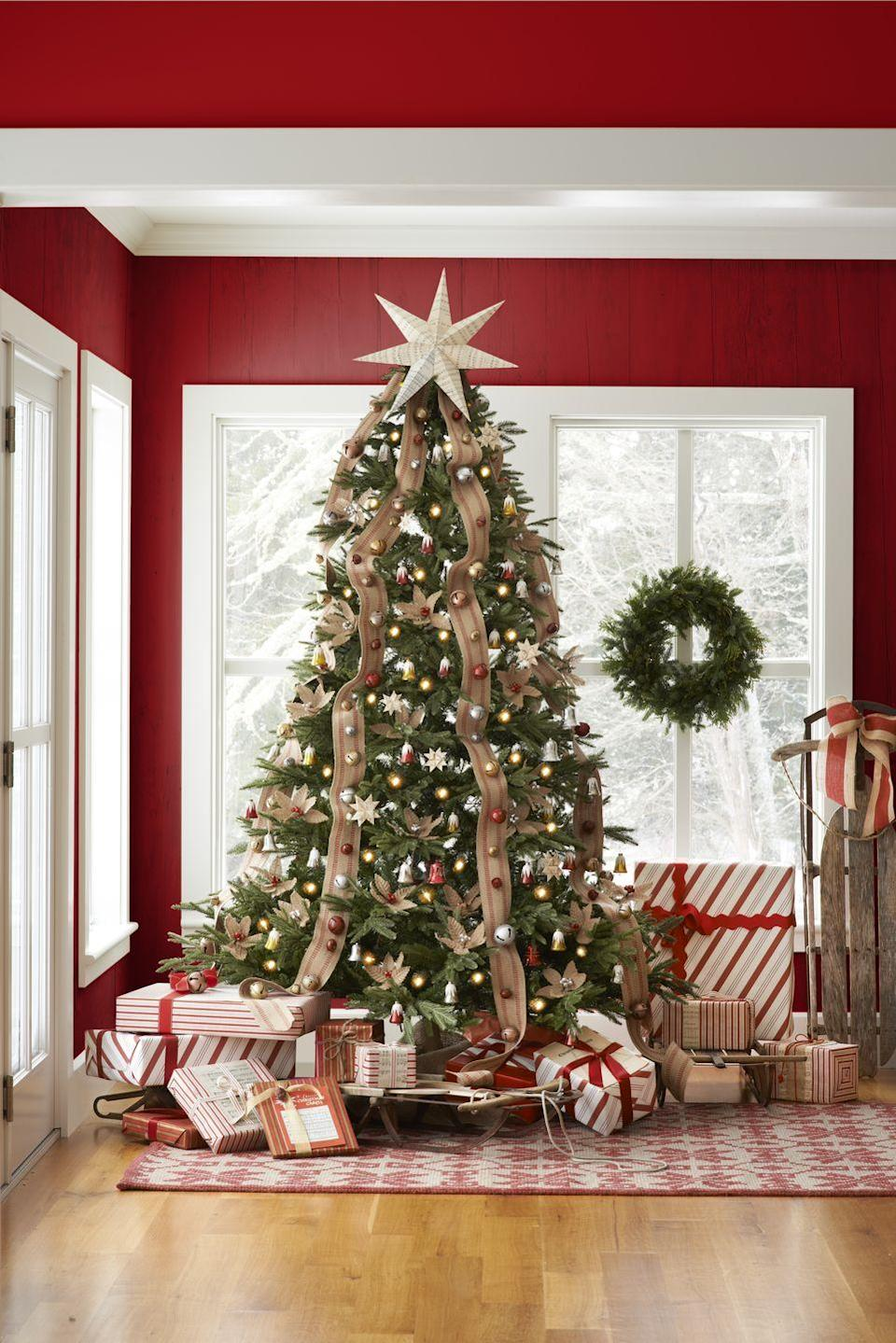 """<p>For a rustic look, cascade striped jute ribbon—such as upholstery webbing—down the complete height of your Christmas tree. Add additional holiday charm by attaching jingle bells to the ribbon with glue or a few simple stitches. </p><p><a class=""""link rapid-noclick-resp"""" href=""""https://www.amazon.com/Upholstery-Craft-Jute-Webbing-Rolls/dp/B07BQB2L6X/ref=sr_1_4?tag=syn-yahoo-20&ascsubtag=%5Bartid%7C10050.g.28703522%5Bsrc%7Cyahoo-us"""" rel=""""nofollow noopener"""" target=""""_blank"""" data-ylk=""""slk:SHOP JUTE UPHOLSTERY WEBBING"""">SHOP JUTE UPHOLSTERY WEBBING</a><br></p>"""