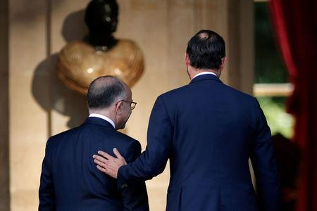 Newly-appointed French Prime Minister Edouard Philippe (R) puts his hand on the shoulder of his predecessor Bernard Cazeneuve (L) during a handover ceremony at the Hotel Matignon, in Paris, France, May 15, 2017.    REUTERS/Benoit Tessier