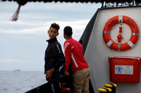 Tunisian migrants stand on the German NGO Sea-Eye migrant rescue ship 'Alan Kurdi' after they were informed they would disembark in Malta, in international waters off Malta in the central Mediterranean Sea