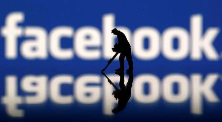 A figurine is seen in front of the Facebook logo in this illustration