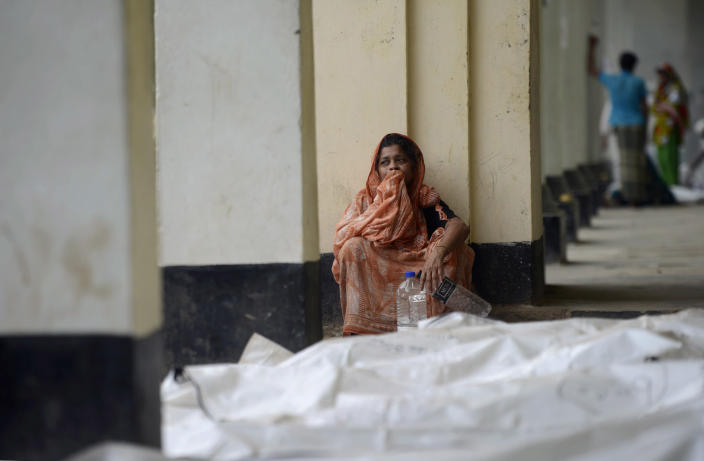 A Bangladeshi woman mourns as she sits beside the body of a relative after identifying it at a makeshift morgue in Savar, near Dhaka, Bangladesh, Saturday, May 11, 2013. The death toll from Bangladesh's worst industrial disaster is more than 1,000 and climbing. More than 2,500 people were rescued in the immediate aftermath of the April 24 disaster. (AP Photo/Ismail Ferdous)