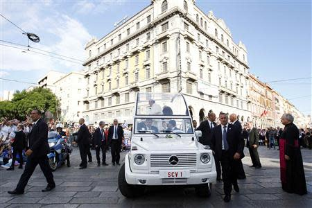 Bodyguards escort Pope Francis as the faithful welcome his arrival in his Pope-mobile for a meeting with youths in Cagliari