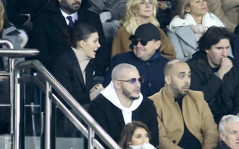 PARIS, FRANCE - NOVEMBER 28: Leonardo DiCaprio and his girlfriend Camila Morrone, below DJ Snake attend the UEFA Champions League Group C match between Paris Saint-Germain (PSG) and Liverpool FC at Parc des Princes stadium on November 28, 2018 in Paris, France. (Photo by Jean Catuffe/Getty Images)