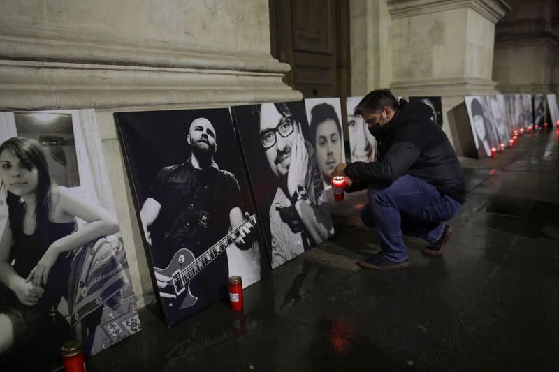 Activist Marian Raduna lights a candle in front a portrati of one of the victims of the Colectiv fire,