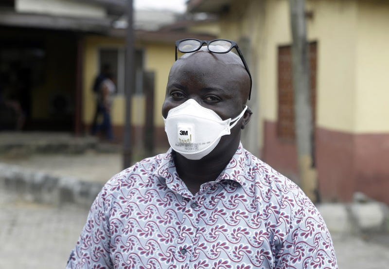 A man wearing a face mask walks outside Yaba Mainland hospital where an Italian citizen - the country's first case of the COVID-19 virus - is being treated, in Lagos, Nigeria Friday, Feb. 28, 2020. Nigeria's health authorities have reported the country's first case of a new coronavirus in Lagos, the first confirmed appearance of the disease in sub-Saharan Africa. (AP Photo/ Sunday Alamba)