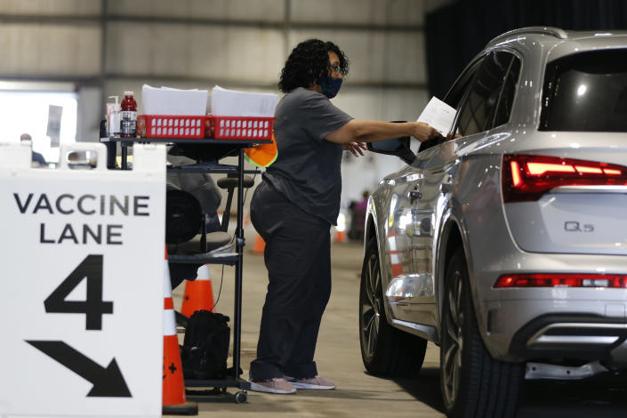Judy Shavers administers a coronavirus vaccine at the drive-thru clinic Thursday, June 10, 2021, in Columbus, Ohio. The U.S. is confronted with an ever-growing surplus of COVID-19 vaccines, looming expiration dates and stubbornly lagging demand at a time when the developing world is clamoring for doses to stem a rise in infections. (AP Photo/Jay LaPrete)