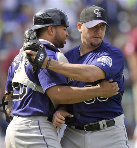 Colorado Rockies closing pitcher Rafael Betancourt right, celebrates with catcher Wilin Rosario after the Rockies defeated the Chicago Cubs 4-3 in a baseball game in Chicago, Saturday, Aug. 25, 2012. (AP Photo/Paul Beaty)