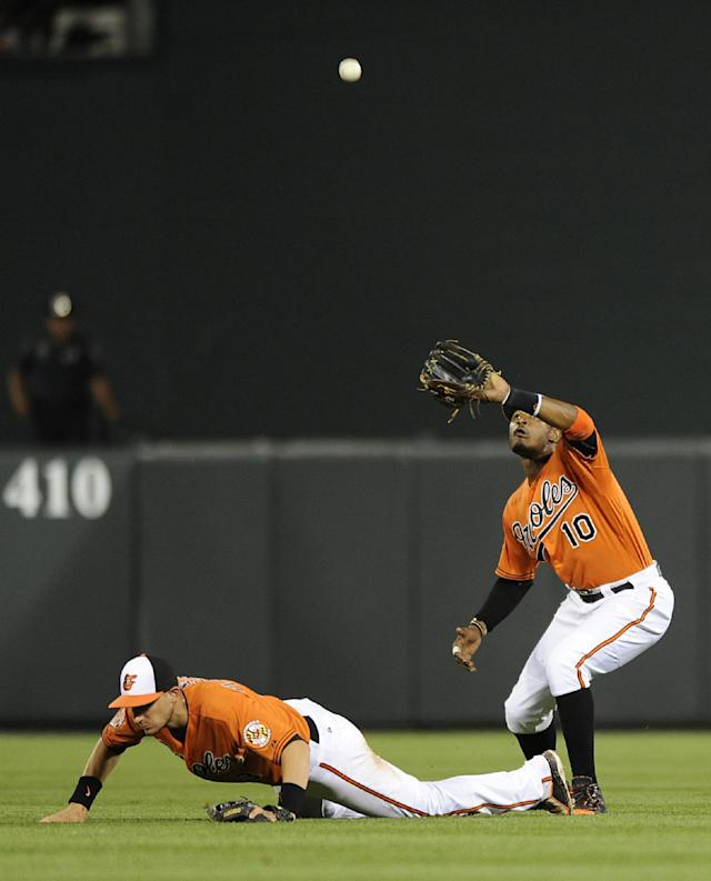 Baltimore Orioles center fielder Adam Jones, right, catches a shallow fly ball hit by Oakland Athletics' Alberto Callaspo as second baseman Ryan Flaherty stumbles during the eighth inning of a baseball game Saturday, June 7, 2014, in Baltimore. The Orioles won 6-3. (AP Photo/Gail Burton)