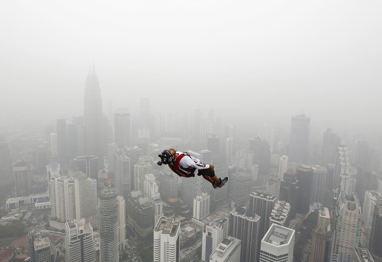 A BASE jumper leaps from the 300-metre high Kuala Lumpur Tower during the International Tower Jump in which more than 100 people take part, on a hazy day in Kuala Lumpur, Malaysia October 2, 2015. Slash-and-burn agriculture in neighbouring Indonesia has blanketed Malaysia and Singapore in a choking haze for weeks. REUTERS/Olivia Harris      TPX IMAGES OF THE DAY