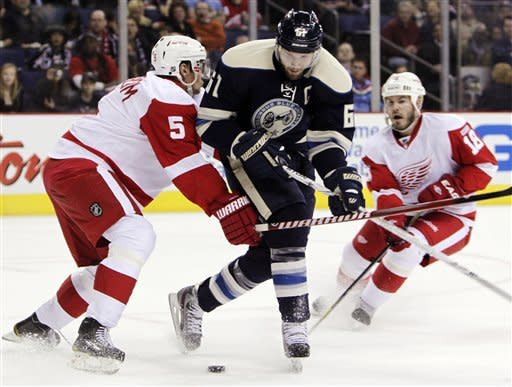 Columbus Blue Jackets' Rick Nash, center, tries to skate between Detroit Red Wings' Niklas Lidstrom, left, of Sweden, and Ian White during the second period of an NHL hockey game, Wednesday, March 28, 2012, in Columbus, Ohio. (AP Photo/Jay LaPrete)