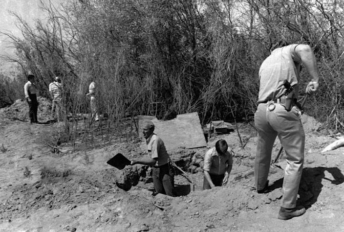 FILE - In this July 17, 1976 file photo. members of the Alameda County Crime Lab and FBI are pictured working around the opening to the van where 26 Chowchilla school children and their bus driver were held captive at a rock quarry near Livermore, Calif.  Ed Ray, the school bus driver hailed as a hero for helping 26 students escape after three men kidnapped the group and buried the entire bus underground in 1976 died on Thursday, May 17, 2012. He was 91.  (AP Photo)