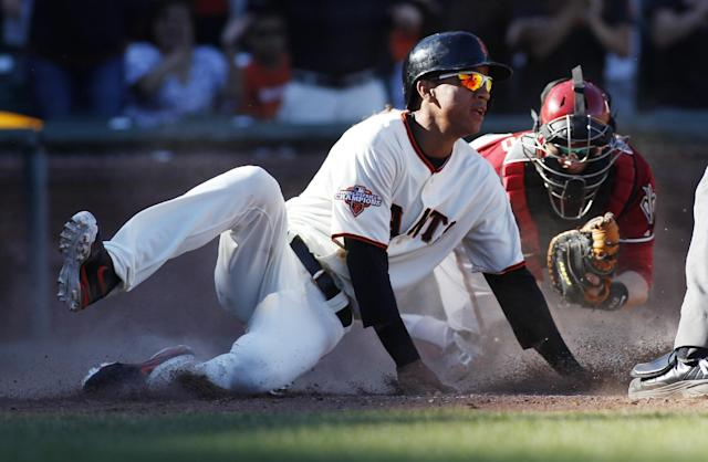 San Francisco Giants' Ehire Adrianza, front, scores in front of Arizona Diamondbacks catcher Miguel Montero during the 11th inning of a baseball game, Sunday, Sept. 8, 2013, in San Francisco. The Giants defeated the Diamondbacks 3-2 in 11 innings. (AP Photo/George Nikitin)