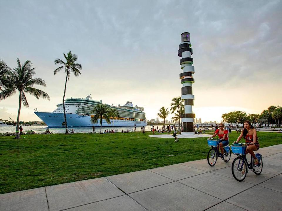 Two people bike down the sidewalk as Royal Caribbean International's Freedom of the Seas cruise ship sets off down Government Cut past South Pointe Park for a simulated voyage leaving from PortMiami in Miami, Florida, on Sunday, June 20, 2021. In accordance with CDC requirements, the purpose of the simulation is to observe the cruise line's multilayered health and safety measures.