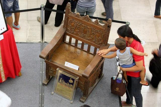 A mother & son touch the papal chair used by Blessed Pope John Paul II in 1981, which is on display at the Activity Area of the Gateway Mall in Quezon City. From October 9-21, the relics and photo exhibit of newly Blessed Pope John Paul II will be displayed for public viewing by Araneta Center and Diocese of Cubao in celebration of the upcoming first feast day of the newly Blessed Pope John Paul II which falls on October 22. (Jhun Dantes Jr/NPPA Images)