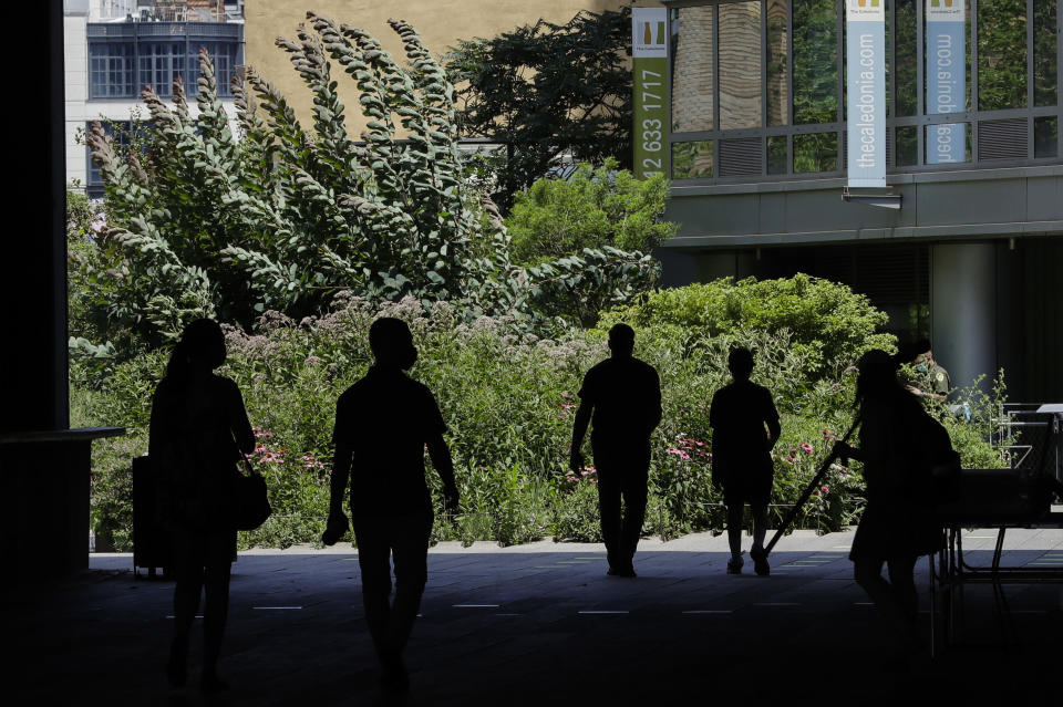 FILE - In this July 16, 2020, file photo people walk along the High Line Park in New York. Nearly half of Americans whose families experienced layoffs during the pandemic now believe their lost jobs will not return, a new poll from The Associated Press-NORC Center for Public Affairs Research shows, as temporary layoffs give way to shuttered businesses, bankruptcies and lasting payroll cuts. (AP Photo/Frank Franklin II, File)