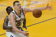 Denver Nuggets center Nikola Jokic (15) reaches for the ball while defended by Golden State Warriors forward Draymond Green during the second half of an NBA basketball game in San Francisco, Monday, April 12, 2021. (AP Photo/Jeff Chiu)