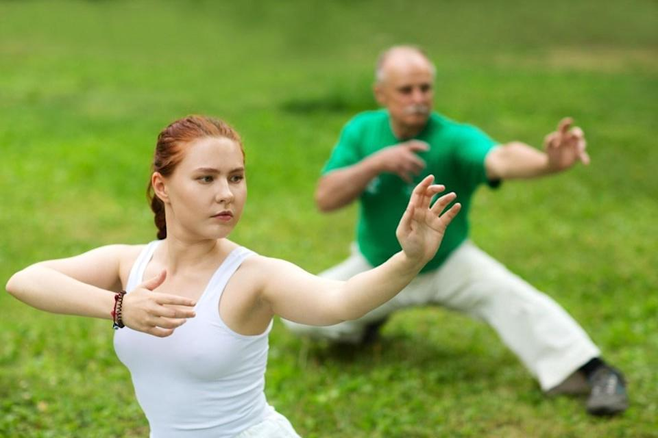 group of people practice Tai Chi Chuan in a park