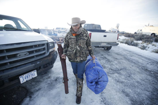 In this Jan. 6, 2016 photo, Arizona rancher LaVoy Finicum carries his rifle after standing guard all night at the Malheur National Wildlife Refuge near Burns, Ore. (AP photo/Rick Bowmer)