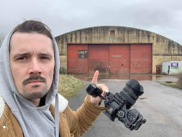 Chris Lloyd in front of a hangar at Llandow airfield, where Trafford was training to fly Spitfires.