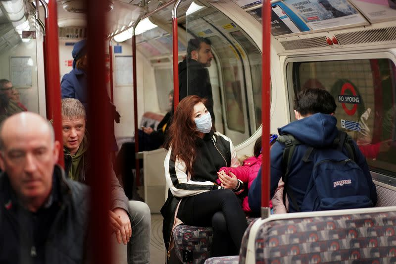 A woman wears a protective face mask on the London Underground in central London