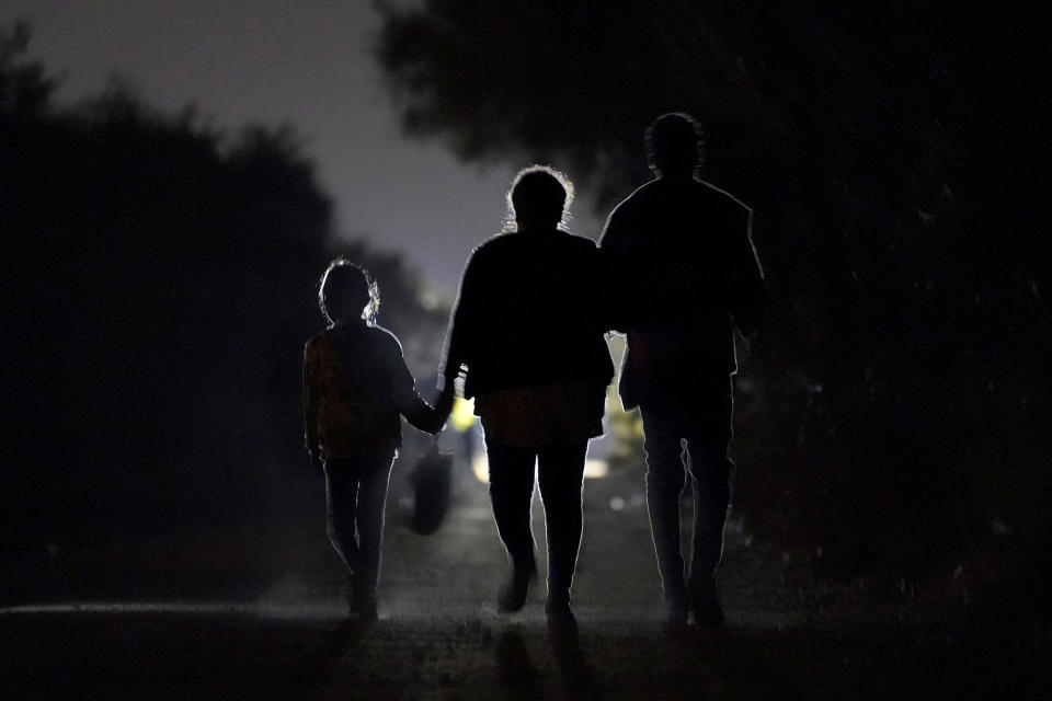 A 7-year-old migrant girl from Honduras, left, walks with Fernanda Solis, 25, center, also of Honduras, and an unidentified man as they approach a U.S. Customs and Border Protection processing center to turn themselves in while seeking asylum moments after crossing the U.S.-Mexico border, Sunday, March 21, 2021, in Mission, Texas. The girl's journey illustrates the extraordinary risks taken by parents to get their children across the border, even if it means abandoning them for the most perilous part of the trip. She is one of thousands of kids arriving alone in the U.S. in a surge that is straining the federal government's system for managing refugees. (AP Photo/Julio Cortez)