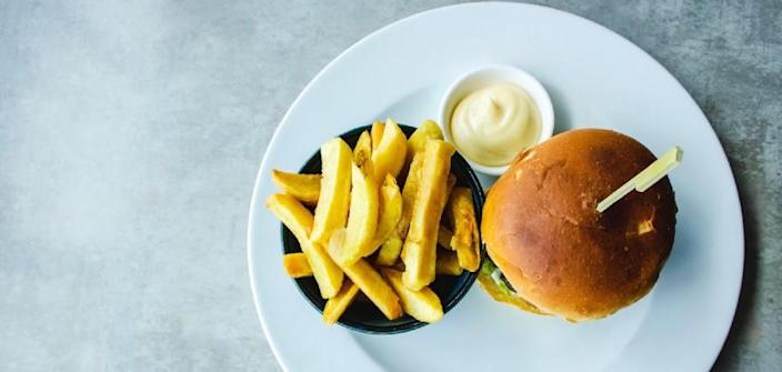 A burger, fries and mayo cup