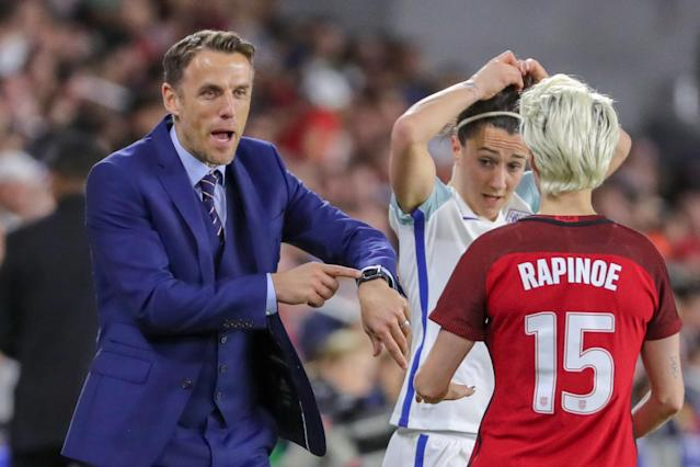 England coach Phil Neville (left) shows United States forward Megan Rapinoe the watch Rapinoe accidentally broke during the 2018 SheBelieves Cup. (Joe Petro/Getty)