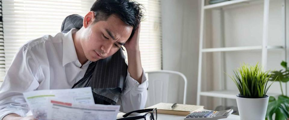 Stressed young asian businessman holding so many expenses bills such as electricity bill,water bill,internet bill,cell phone bill and credit card bill in his hand no money to pay debt