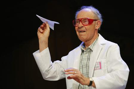 Chemist Dudley Herschbach, winner of the 1986 Nobel Prize for Chemistry, throws a paper airplane during the 23rd First Annual Ig Nobel Prize ceremony at Harvard University in Cambridge, Massachusetts September 12, 2013. REUTERS/Brian Snyder