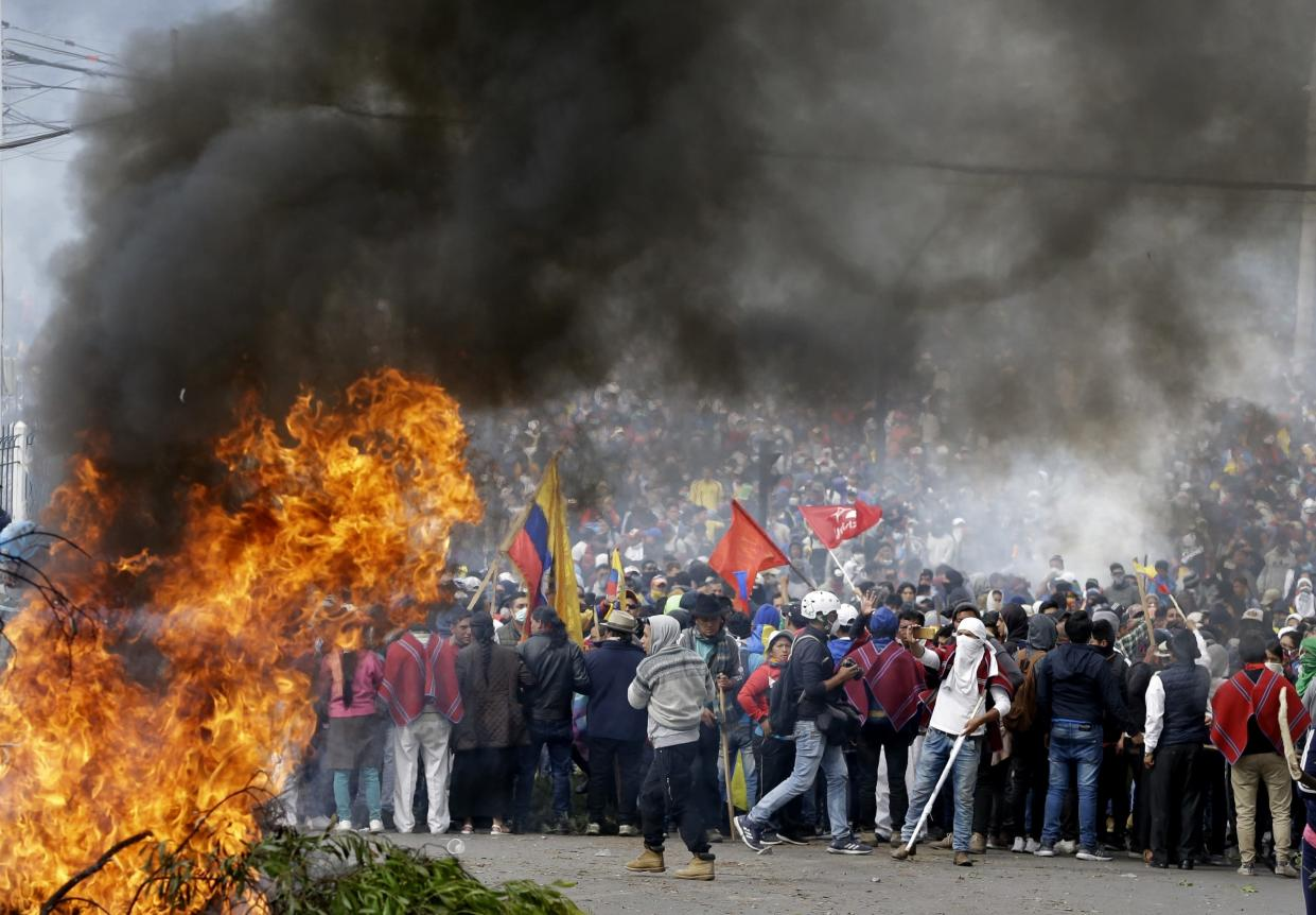 Anti-government demonstrators gather behind a burning barricade during a protest against President Lenin Moreno and his economic policies, in Quito, Ecuador, Oct. 8, 2019. (Photo: Fernando Vergara/AP)