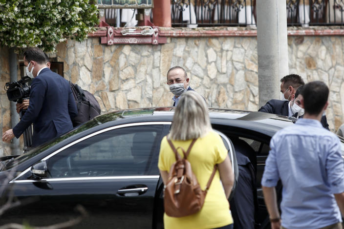 """Turkish Foreign Minister Mevlut Cavusoglu, center, arrives at a restaurant at village Thamna, near Komotini, in northeastern Greece, Sunday, May 30, 2021. Greece's prime minister said Friday his country is seeking improved ties with neighbor and longtime foe Turkey, but that the onus is on Turkey to refrain from what he called """"provocations, illegal actions and aggressive rhetoric."""" (AP Photo/Giannis Papanikos)"""
