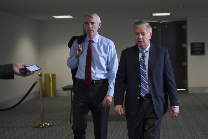 Sen. Rob Portman, R-Ohio,, left, and Sen. Lindsey Graham, R-S.C., right, leave a Republican policy lunch on Capitol Hill in Washington, Thursday, March 19, 2020. (AP Photo/Susan Walsh)