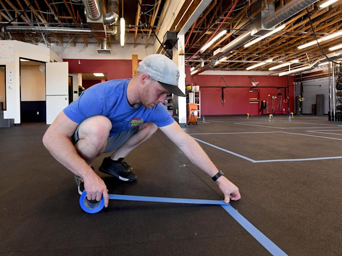 Co-owner Chad Cole tapes down 7-by-7-foot social distancing boxes as preparations are made to open for business at CrossFit Apollo, which has been closed since March 17 due to the statewide shutdown because of the coronavirus (COVID-19) pandemic on May 28, 2020 in Las Vegas, Nevada