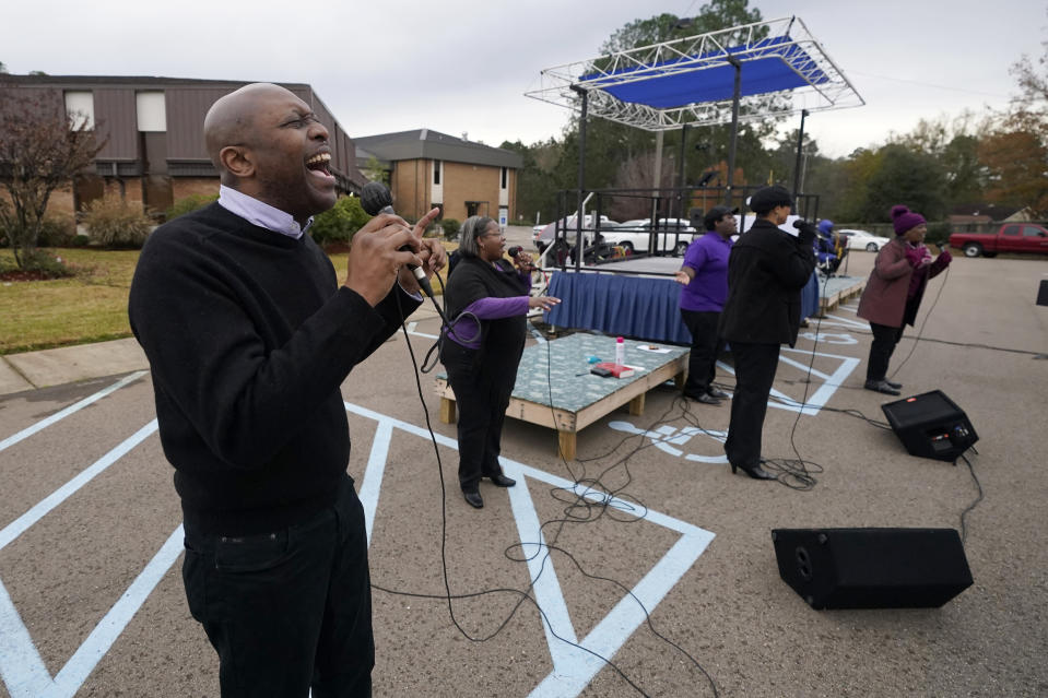 Choir member Ron Garry joins others in an opening song during First Sunday service at Anderson United Methodist Church, Dec. 6, 2020, in Jackson, Miss. The church has taken to using digital means by which to broadcast the majority of its services. However, following covid protocol, the congregants gather in the church's parking lot the first Sunday of each month to celebrate the receiving of communion in their private vehicles. (AP Photo/Rogelio V. Solis)