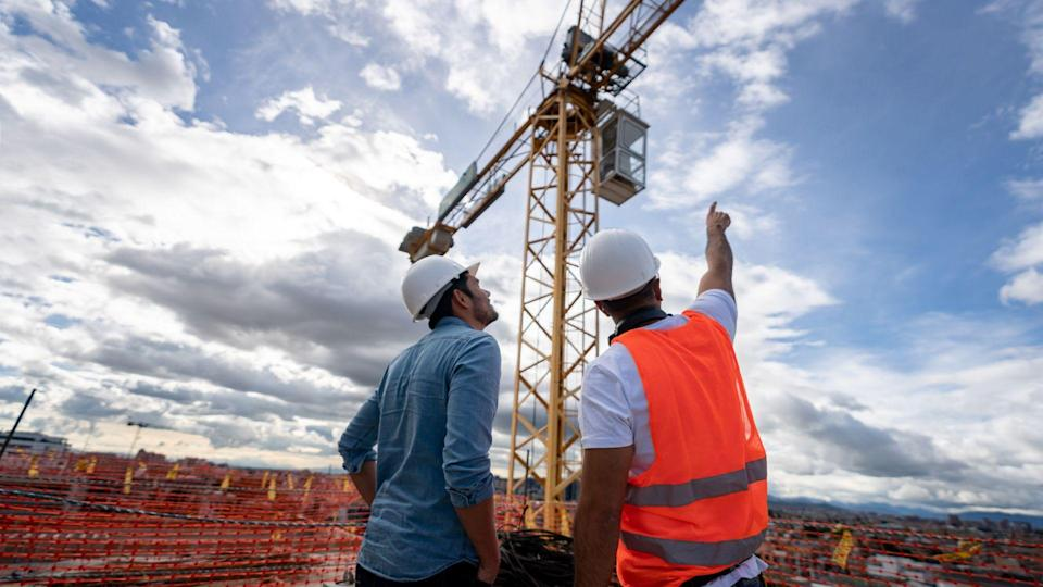 Architects looking at the view from a construction site and pointing at a crane.