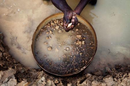 FILE PHOTO: An artisanal miner pans for diamonds in the town of Koidu, in eastern Sierra Leone April 21, 2012. REUTERS/Finbarr O'Reilly/File Photo