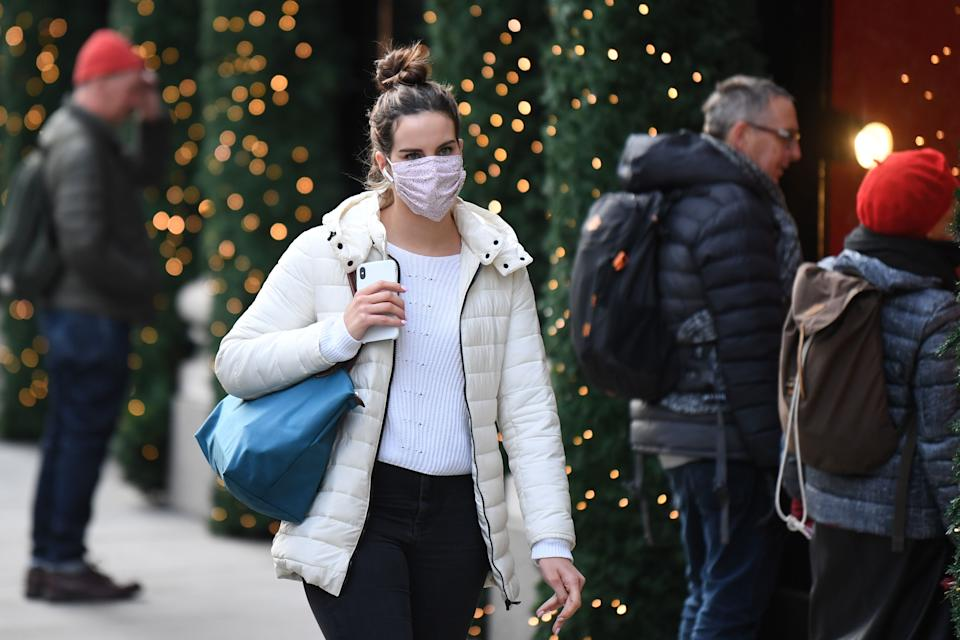 A pedestrian wearing a mask because of the novel coronavirus pandemic walks past shops with Christmas decorations on Oxford Street in London on November 26, 2020. - London will escape the tightest restrictions once England's national coronavirus lockdown ends next week, the government said Thursday, but major cities including Manchester and Birmingham face at least two more weeks of tough rules. England will return to a regional tiered system when the national regulations end on December 2, with those areas suffering the worst case rates entering the highest Tier 3. (Photo by DANIEL LEAL-OLIVAS / AFP) (Photo by DANIEL LEAL-OLIVAS/AFP via Getty Images)