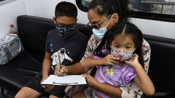 PHOTO: A boy waits while his mother signs a form required for him to receive a shot of the Pfizer COVID-19 vaccine at a mobile vaccination site on May 22, 2021, in Orlando, Fla. (Paul Hennessy/NurPhoto via AP, FILE)