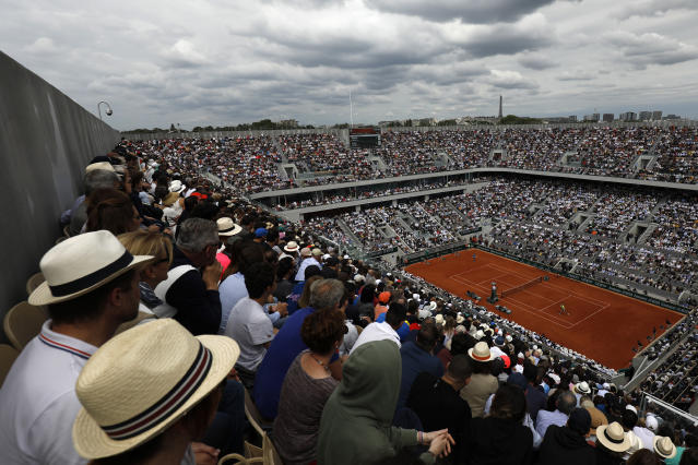 Spectators watch Austria's Dominic Thiem playing Spain's Rafael Nadal, right, on center court during the men's finalmatch of the French Open tennis tournament at the Roland Garros stadium in Paris, Sunday, June 9, 2019. (AP Photo/Pavel Golovkin)