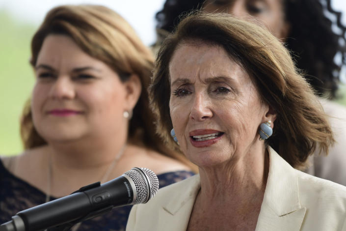 House Democratic Leader Nancy Pelosi speaks at a joint press conference with members of a Congressional delegation, including resident commissioner Jennifer González, left, at the Roque Díaz Tizol School in Yabucoa, Puerto Rico, Friday, July 27, 2018. Pelosi is pledging to help speed up Puerto Rico's hurricane recovery process after a two-day visit to the U.S. territory. (AP Photo/Carlos Giusti)