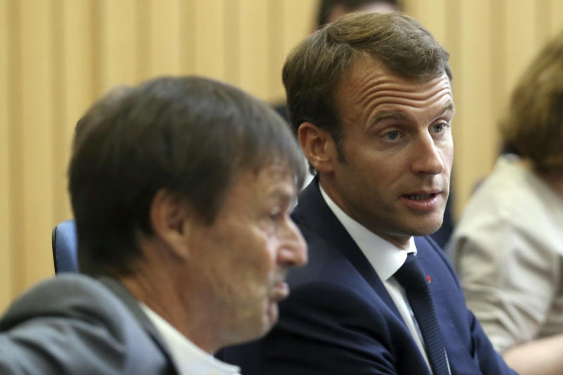 FILE - In this Friday, July 27, 2018 file picture French President Emmanuel Macron, right, flanked with French Minister of the Ecological and Social Transition Nicolas Hulot, left, attends a summit for Energy Interconnections at the European Maritime Safety Agency headquarters in Lisbon, Portugal. France's high-profile environment minister, former TV personality Nicolas Hulot, has unexpectedly announced his resignation live on national radio, dealing a blow to the lofty green ambitions of President Emmanuel Macron. (AP Photo/Armando Franca, File)