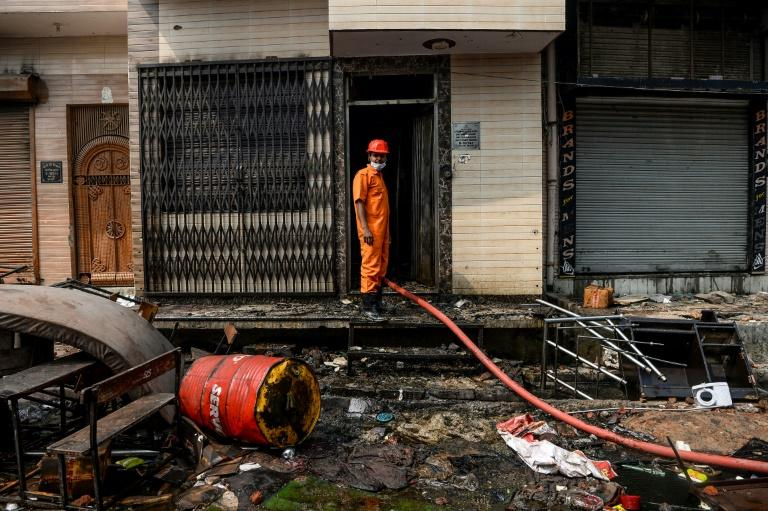 A firefighter stands in the entrance of a New Delhi residence on February 26 following clashes that have claimed more than 25 lives