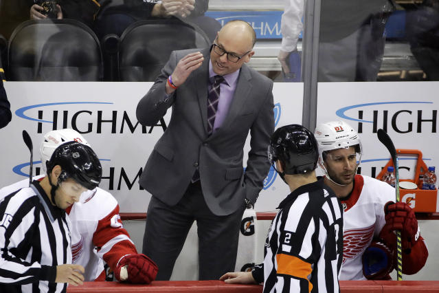 Detroit Red Wings head coach Jeff Blashill, center, talks with referee Mike Hasenfratz (2) during the first period of the team's NHL hockey game against the Pittsburgh Penguins in Pittsburgh, Sunday, Feb. 16, 2020. (AP Photo/Gene J. Puskar)