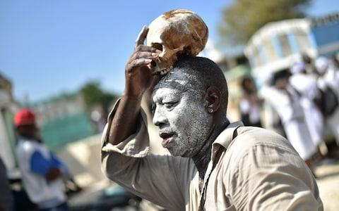 A voodoo devotee with a skull on top of his head is seen during ceremonies honoring the Haitian voodoo spirit of Baron Samdi and Gede on the Day of the Dead in the Cementery of Cite Soleil, in Port-au-Prince, Haiti on November 1, 2017 - Credit: AFP