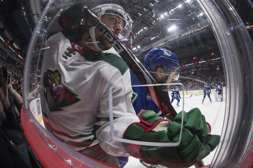 Minnesota Wild's Mats Zuccarello, left, is checked by Vancouver Canucks' Alexander Edler, of Sweden, during the first period of an NHL hockey game Wednesday, Feb. 19, 2020, in Vancouver, British Columbia. (Darryl Dyck/The Canadian Press via AP)