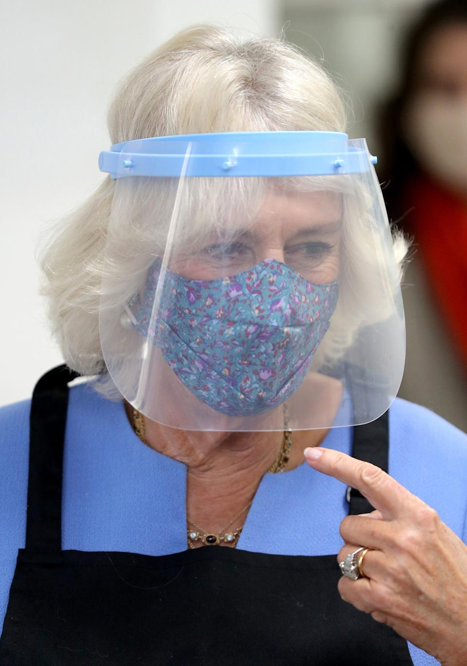 RICKMANSWORTH, ENGLAND - OCTOBER 08: Camilla, Duchess of Cornwall, in her role as President of the Royal Voluntary Service, wears a face shield as she helps serving meals during a visit to The Royal Voluntary Service Lunch Club on October 8, 2020 in Rickmansworth, England. (Photo by Andrew Matthews - WPA Pool/Getty Images)