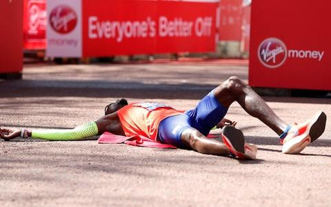 Mo Farah lies on the floor at the finish with exhaustion - Credit: REUTERS