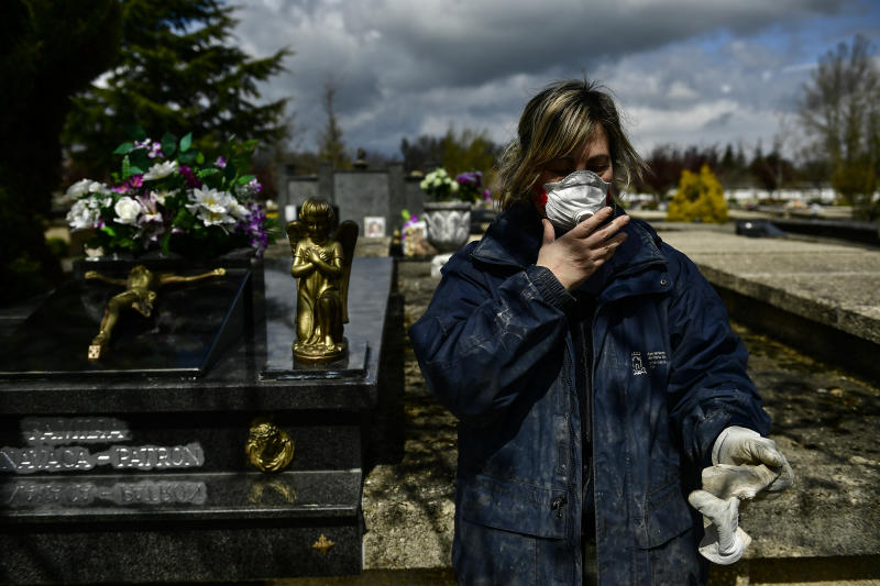 Undertaker Mari Carmen Serrador, 53 years old, protecting herself with a mask at Salvador cemetery during the coronavirus outbreak, near to Vitoria, northern Spain, Monday, March 30, 2020. The new coronavirus causes mild or moderate symptoms for most people, but for some, especially older adults and people with existing health problems, it can cause more severe illness or death. AP Photo/Alvaro Barrientos)