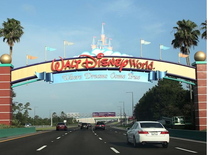 <p>Visitors drive past a sign welcoming them to Walt Disney World on the first day of reopening of the iconic Magic Kingdom theme park in Orlando, Florida, on 11 July 2020</p> ((Photo by GREGG NEWTON/Gregg Newton/AFP via Getty Images))